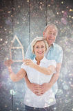 Composite image of happy older couple holding house shape. Happy older couple holding house shape against white snow and stars on black Royalty Free Stock Images