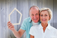 Composite image of happy older couple holding house shape. Happy older couple holding house shape against wooden planks Royalty Free Stock Image
