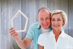 Composite image of happy older couple holding house shape Royalty Free Stock Image