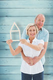Composite image of happy older couple holding house shape. Happy older couple holding house shape against wooden planks Stock Images