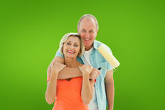 Composite image of happy older couple holding paint roller Stock Photos