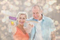 Composite image of happy older couple holding paintbrushes Stock Photo