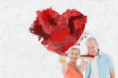 Composite image of happy older couple holding paintbrushes Stock Images
