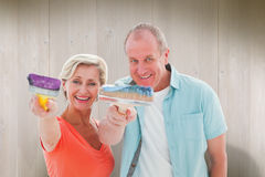 Composite image of happy older couple holding paintbrushes Royalty Free Stock Photos