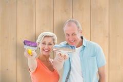 Composite image of happy older couple holding paintbrushes Stock Photos