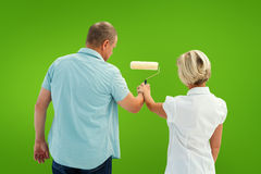 Composite image of happy older couple painting white wall Stock Photo