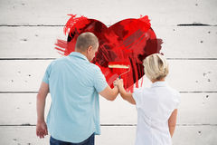 Composite image of happy older couple painting white wall Royalty Free Stock Images