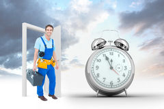 Composite image of happy plumber carrying tool box. Happy plumber carrying tool box against alarm clock counting down to twelve Royalty Free Stock Photo