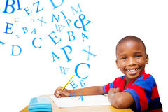 Composite image of happy pupil at desk Stock Photo