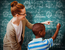 Composite image of happy pupil and teacher. Happy pupil and teacher against green chalkboard Royalty Free Stock Photography