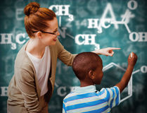Composite image of happy pupil and teacher. Happy pupil and teacher against green chalkboard Stock Photography