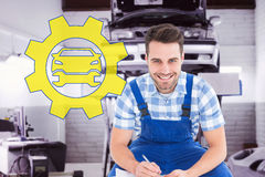 Composite image of happy repairman crouching while writing on clipboard Royalty Free Stock Image