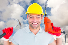 Composite image of happy repairman holding hammer and drill machine Royalty Free Stock Photo