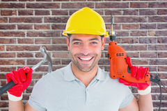 Composite image of happy repairman holding hammer and drill machine Stock Images