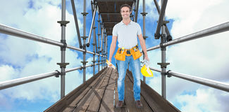 Composite image of happy repairman holding spirit level and hardhat 3d Royalty Free Stock Images