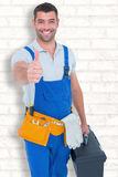 Composite image of happy repairman with toolbox gesturing thumbs up Royalty Free Stock Image