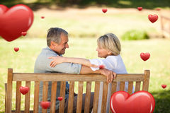 Composite image of happy retired couple sitting on the bench Stock Photo