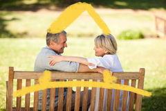 Composite image of happy retired couple sitting on the bench Royalty Free Stock Images