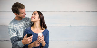 Composite image of happy romantic couple with mobile phone Royalty Free Stock Photography