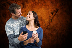 Composite image of happy romantic couple with mobile phone Stock Photography