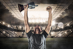 Composite image of happy rugby player holding trophy Royalty Free Stock Photo