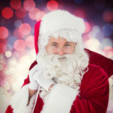Composite image of happy santa claus holding his sack Royalty Free Stock Image