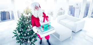 Composite image of happy santa claus holding pile of gifts Stock Photo