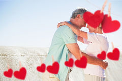Composite image of happy senior couple embracing on the pier Royalty Free Stock Images