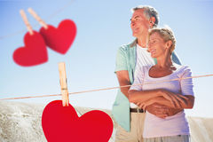 Composite image of happy senior couple embracing on the pier Stock Photography