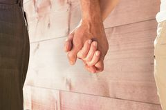 Composite image of happy senior couple holding hands Stock Image