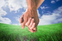 Composite image of happy senior couple holding hands Stock Photo