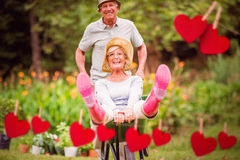 Composite image of happy senior couple playing with a wheelbarrow Stock Images