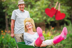 Composite image of happy senior couple playing with a wheelbarrow Royalty Free Stock Photo