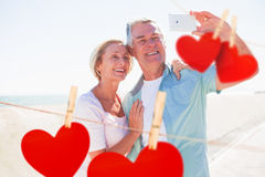 Composite image of happy senior couple posing for a selfie Stock Photos