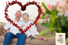 Composite image of happy senior couple relaxing on sofa. Happy senior couple relaxing on sofa against happy valentines day royalty free stock photos