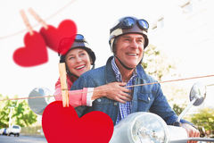 Composite image of happy senior couple riding a moped Stock Image