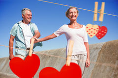 Composite image of happy senior couple walking on the pier Royalty Free Stock Images