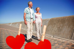 Composite image of happy senior couple walking on the pier Royalty Free Stock Photography