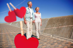 Composite image of happy senior couple walking on the pier Stock Photo