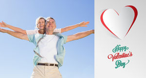 Composite image of happy senior man giving his partner a piggy back. Happy senior men giving his partner a piggy back against cute valentines message Royalty Free Stock Image