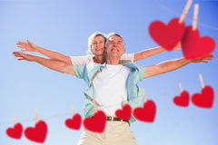 Composite image of happy senior man giving his partner a piggy back. Happy senior men giving his partner a piggy back against hearts hanging on a line Stock Photography
