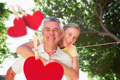 Composite image of happy senior man giving his partner a piggy back. Happy senior men giving his partner a piggy back against hearts hanging on a line Stock Image