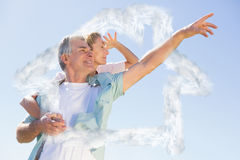 Composite image of happy senior man giving his partner a piggy back. Happy senior men giving his partner a piggy back against house outline in clouds Stock Photography