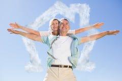 Composite image of happy senior man giving his partner a piggy back. Happy senior men giving his partner a piggy back against house outline in clouds Stock Photo