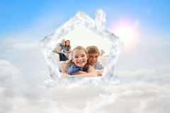 Composite image of happy siblings posing on a carpet with their parents on the background Royalty Free Stock Photos