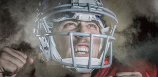 Composite image of happy sportsman cheering while looking up. Happy sportsman cheering while looking up against splashing of powder Stock Photography