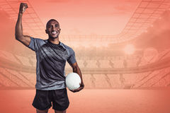 Composite image of happy sportsman with clenched fist holding rugby ball Stock Photography
