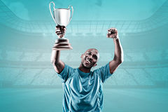 Composite image of happy sportsman looking up and cheering while holding trophy Royalty Free Stock Photo