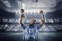 Composite image of happy sportsman looking up and cheering while holding trophy Stock Photography
