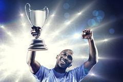 Composite image of happy sportsman looking up and cheering while holding trophy Royalty Free Stock Image